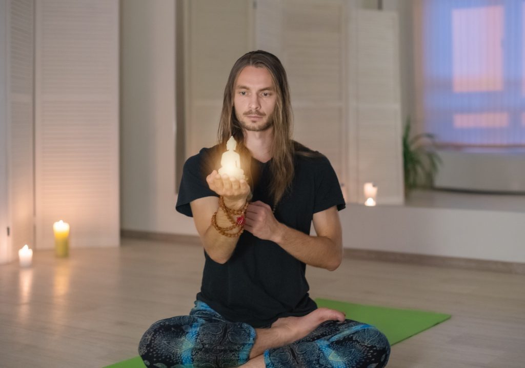 A young male yogi becomes enlightened and holds a Buddha statue in his hands and meditates