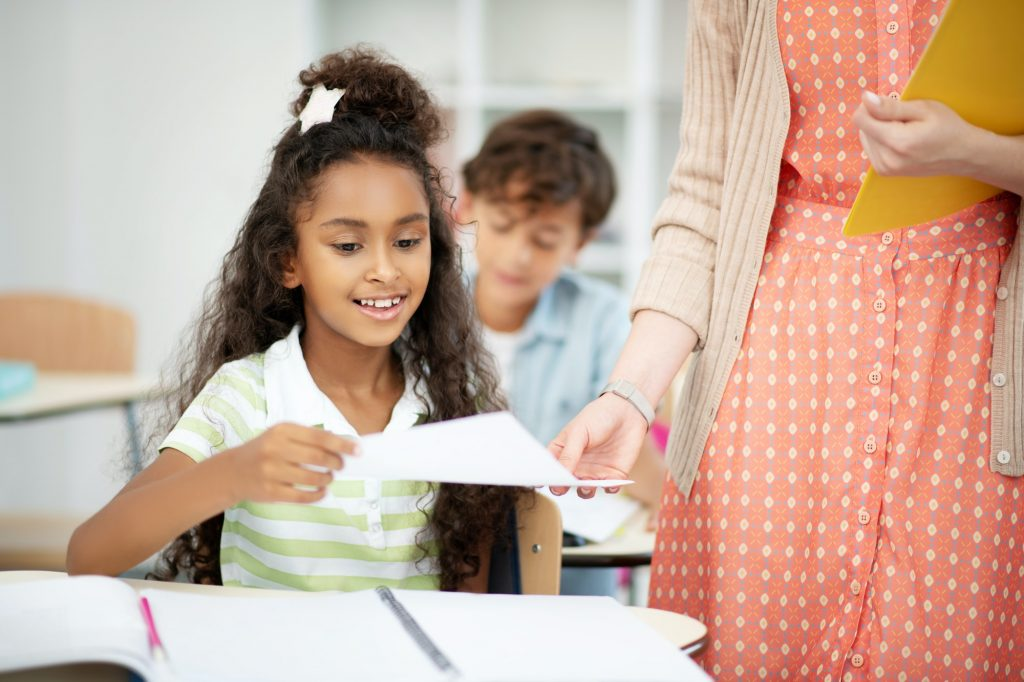 Curly schoolgirl feeling excited before seeing test results
