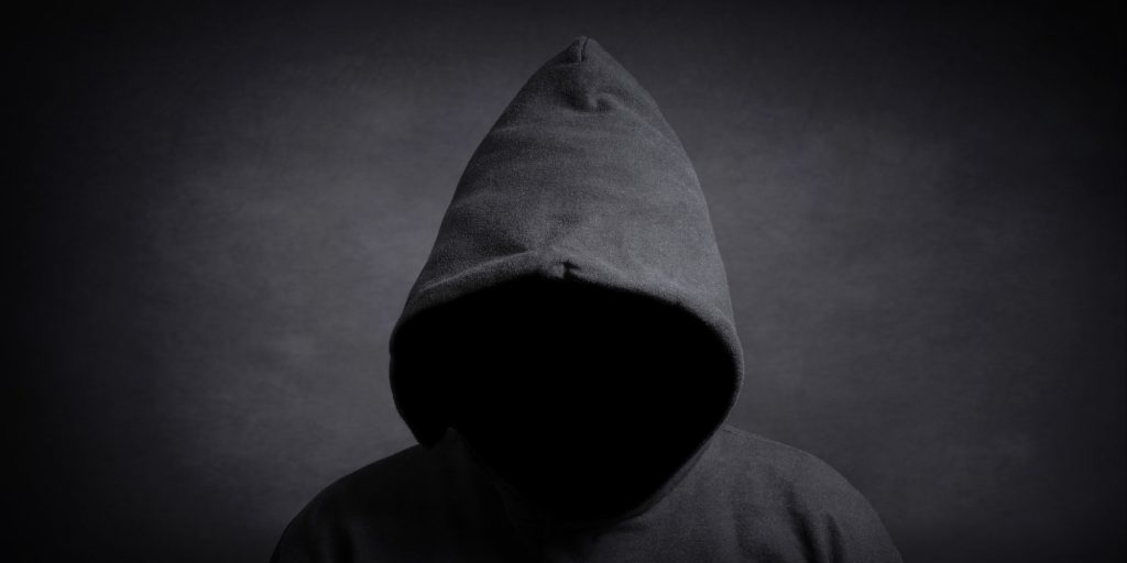 faceless person wearing black hoodie hiding face in shadow. mystery crime or conspiracy concept.