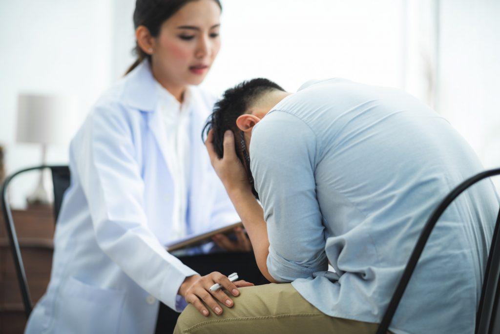 Close-up of psychologist comforting his depressed patient, mental health concept