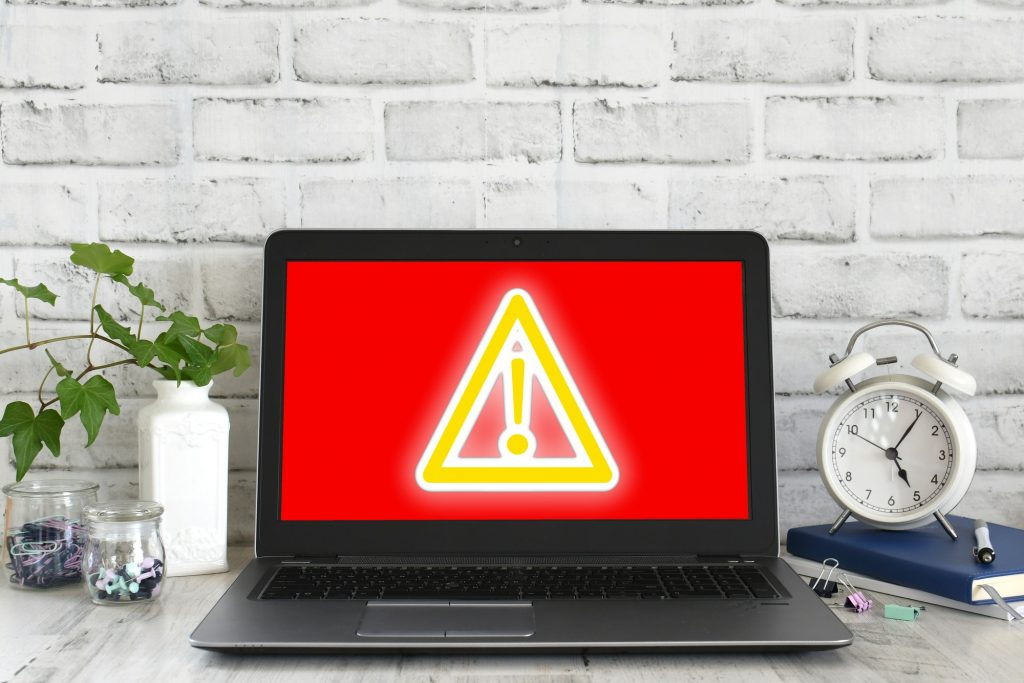 Computer screen showing red screen with yellow glowing danger sign. Concept hack virus cyber attack
